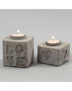 Støpte lysestaker med bokstaver og motiver i relieff