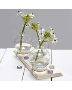Liten vase av glasskule stående på gardinring
