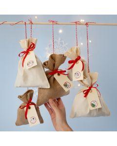 Pakkekalender av stoffposer med tall stickers på manillamerker
