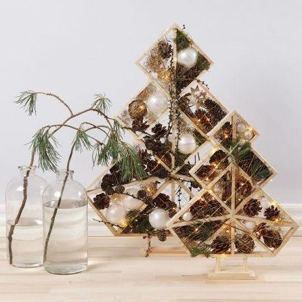 Juletrær pyntet med julekuler, kongler, gran og lys