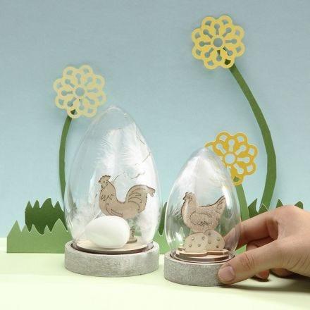 Klokke pyntet med sett-sammen-selv påske trefigurer egg og hvite fjær