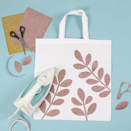 Mulepose dekorert med blad av strykestoff
