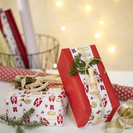 Kreativ julegaveinnpakning med to typer gavepapir og en trefigur