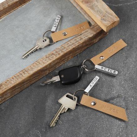 Nøkkelring med preget metallskilt og lærpapirskilt