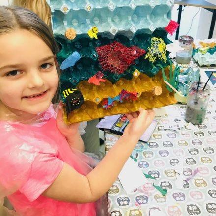 Hav og fisk av dekorerte eggbrett og plastavfall