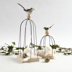 Fugl på fuglebur av trådstenger på treikon