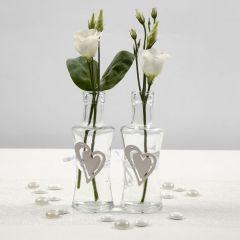 Glassvase med belte av hvitt satengbånd, isatt trehjerte