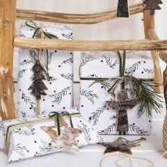 Julegaveinnpakning med grønne grener som motiv pyntet med snor, bånd og gavemerke i naturbark