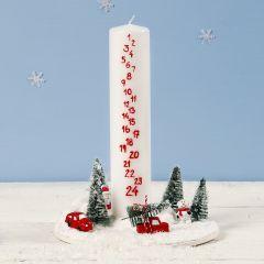 Dekorasjon med kalenderlys omgitt av mini julelandskap