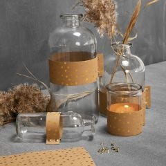 Glassflasker og lysglass dekorert med lærpapir