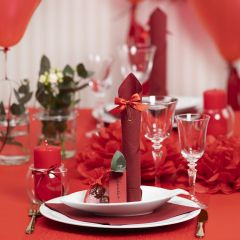 Borddekking og bordpynt i rød med papirblomster, ballonger, serviett brettet som tårn og bordkort