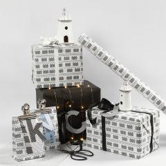 Gaveinnpakning i svart og hvit med fyrtårn og lyskjeder