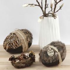 To-delt påskeegg pyntet med naturfjær, kartong og naturhamp