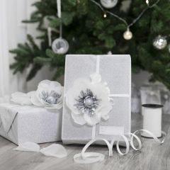 Gaveinnpakning pyntet med blomst av silkepapir