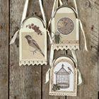 Oppheng av kartong og designpapir i veskebøyle med satengbånd