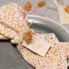 Stoffservietter av patchworkstoff med serviettring og tørkede blomster