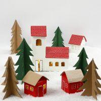 Juleby av melkekartonger og trær av gjenbrukspapp
