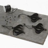 Oppheng av svarte lakkstrimler i snørering med lærsnøre