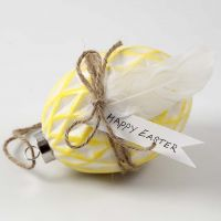 Egg av keramikk malt og pyntet med natursnor og fjær