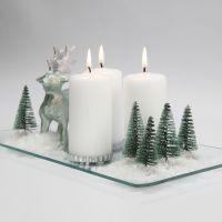 Juledekorasjon med lys, reinsdyr, trær og snø på glassfat