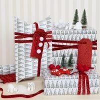 Julegaveinnpakning pyntet med pomponer og minifigurer