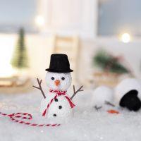 Nissen bygger en snømann foran nissedøren sin