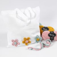 Mulepose pyntet med blomster laget av tubestrikk